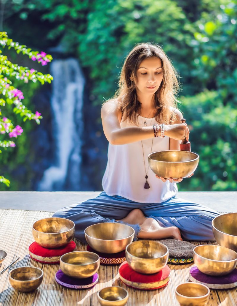 Woman playing on Tibetan singing bowl while sitting on yoga mat against a waterfall. Vintage tonned. Beautiful girl with mala beads meditating.