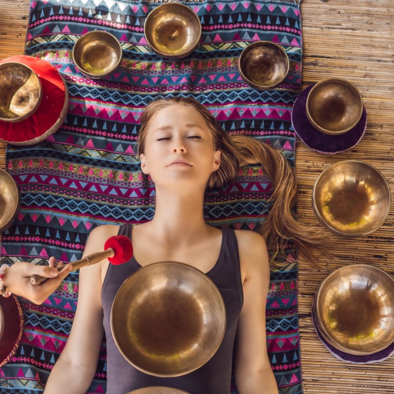 Nepal Buddha copper singing bowl at spa salon. Young beautiful woman doing massage therapy singing bowls in the Spa against a waterfall. Sound therapy, recreation, meditation, healthy lifestyle and body care concept.